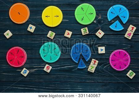 Colorful math fractions on wooden background or table. interesting math for kids. Education, back to school concept. Geometry and mathematics materials. poster