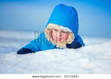 Portrait of a little boy playing in the snow
