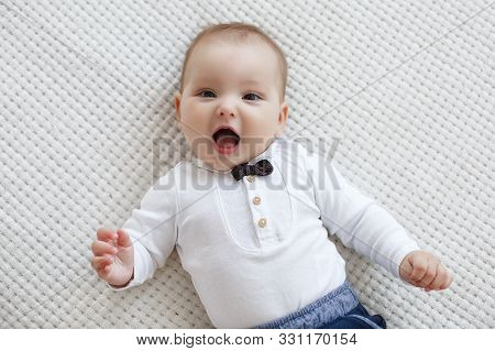 Adorable Baby Boy In White Sunny Bedroom Plays Alone Lying  On The Bed.charming Beautiful Lovely Sma
