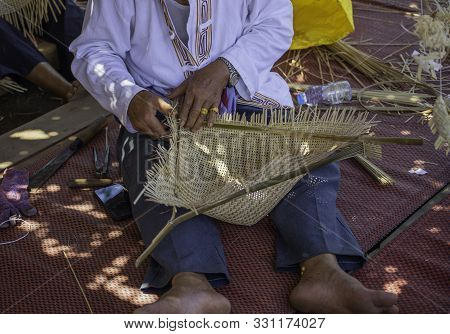 A Skillful Elderly Handicapped Man Do Bamboo Wickerwork By Hands On The Floor. Showing Simply Way Of