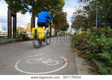 An Urban Bike Route And A Cyclist Motion Blurred Travelling Past In Olympic Village Vancouver.