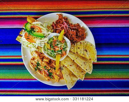 Mexican Food Mix Colorful Background, Guacamole, Cochinita Pibil, Flautas And Quesadilla.
