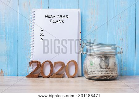 2020 New Year Plans Word On Notebook, Money Glass Jar And Wooden Number. Financial, Resolution, Goal