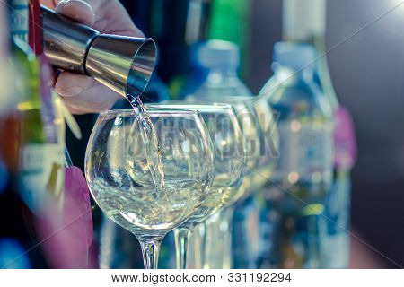 The Bartender's Hand With The Help Of A Dispenser Pours An Alcoholic Drink Into A Glass With Ice. St