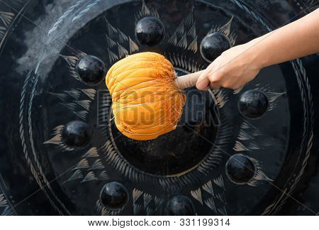 Hand Striking A Metal Gong With An Orange Mallet At An Asian Buddhist Temple - Low View Of An Ancien