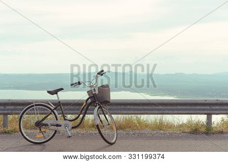 Stationary Bicycle On Cycle Path With Amazing Scenic Views Of A Lake And Mountains - Bike With Baske