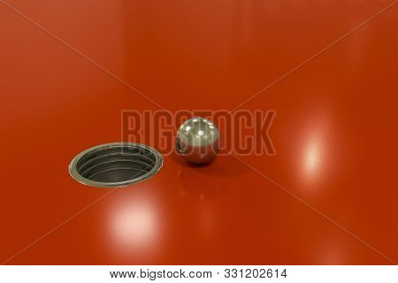 Mettallic Sphere Approaching A Hole On Red Glossy Background
