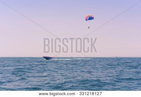 Ocean View Of A Man Parasailing In The Sea Towed By A Speedboat In American Colors - Watersports Sum