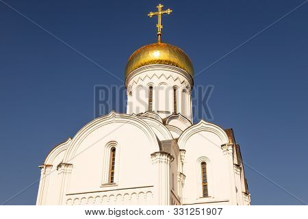 Top Part Of White Eastern Church With Sunlit Gilt Dome Against Dark Blue Sky