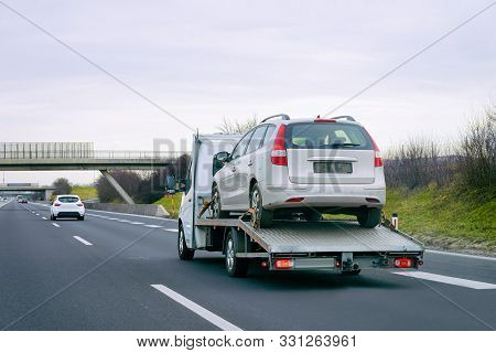 Tow Truck With Car On Warranty On Road