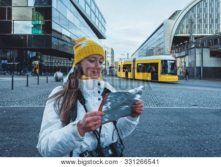 Young Lady Travels With Tourist City Map In Berlin
