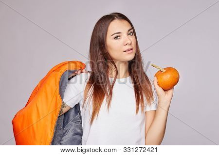 Delighted Young Pretty Woman Returns From Grocers Shop, Holds Fresh Orange Pumpkin, Keeps To Healthy