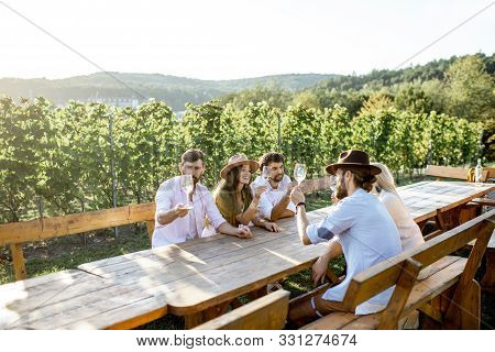 Group Of A Young People Drinking Wine And Talking Together While Sitting At The Dining Table Outdoor