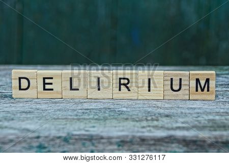 Word Delirium Made Of Wooden Letters On A Gray Table On A Green Background