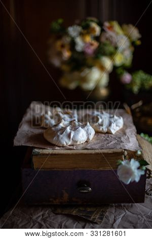 Box from the dresser with book and meringue blanks for Pavlova dessert on it, standing against the background of a bouquet of roses in a brass vase. poster