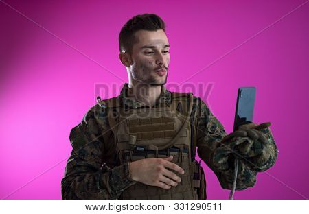 army soldier using smartphone to contact family or girlfriend communication and nostalgia concept pink background poster