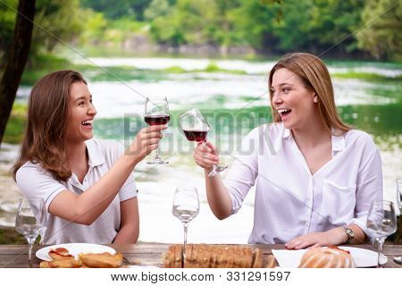 two young happy girlfriends toasting red wine glass while having picnic french dinner party outdoor during summer holiday vacation  near the river at beautiful nature