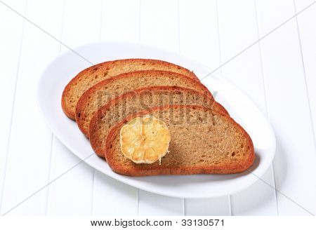 Four toasts with garlic on a white oval plate