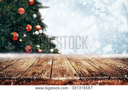 Top Of Empty Wood Table With Beautiful Christmas Tree And Snowfall  Backdrop. Ready For Your Product
