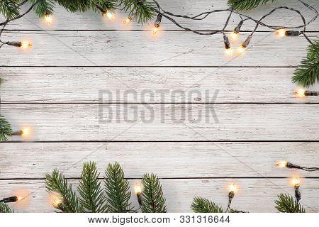 Christmas Lights Bulb And Pine Leaves Decoration On White Wood Plank, Frame Border Design. Merry Chr