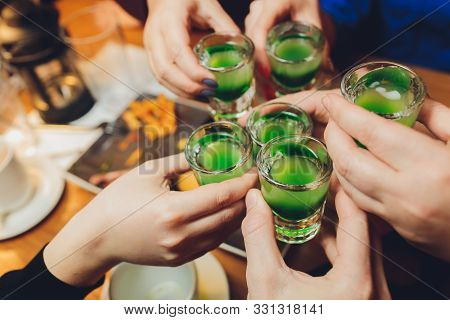 Clinking Glasses With Alcohol And Toasting, Party. Green Alco Shots