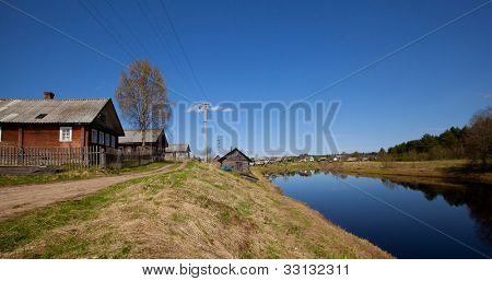 Typical small village near the river in the rays of spring sunshine, in central Russia.