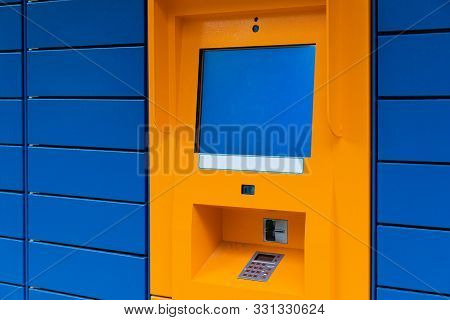 Orange Cashpoint Minibank With Blank Copyspace Screen On Blue Panel Tile Backdrop Angled View