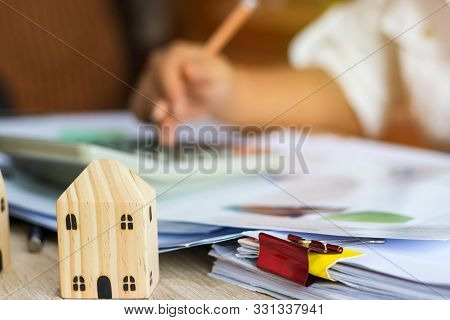 Closeup Of Home And Businesswoman Use Calculator For Analyzing Data Of Market Report For Loan Home.