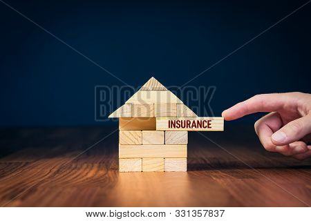 Property (family House) Insurance Protection Concept. Insurance Agent Complete Wooden Model Of The H