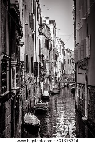 Old Houses With Moored Boats, Venice, Italy. Vertical View Of Narrow Street In Black And White. Vint