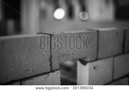 Close Up Of A Brick With Fresh Cement In A Brick Wall, Black And White