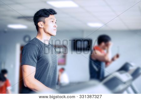 Asian Young Atheletic Man In Sportswear Walking On Treadmill At Gym