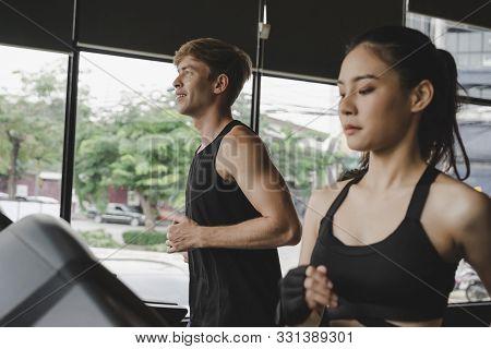 Running. Asian Young People Handsome Man Slim Body Jogging Run Cardio Training On Treadmill Machine