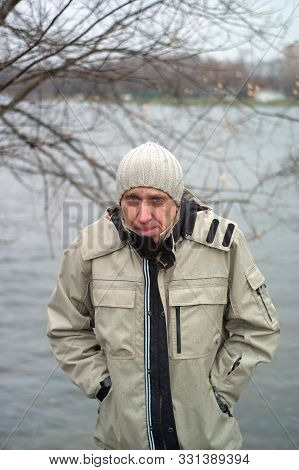A Man Huddled From Cold,  Posing Outdoor, Vertical Shot