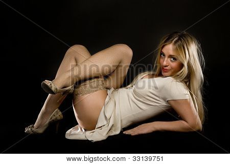young woman in stockings with legs crossed on a black background