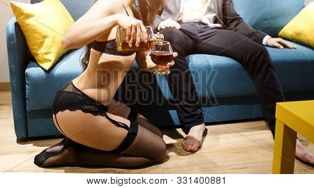 Young Sexy Couple In Living Room. Cut View Of Woman In Black Lingerie Pouring Wiskie Into Glass. Man