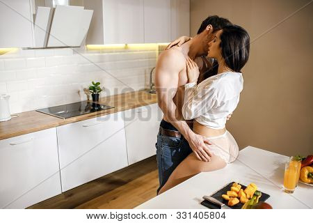 Young Sexy Couple Have Intimacy In Kitchen In Night. Shirtless Well-built Guy Lean To Woman And Kiss