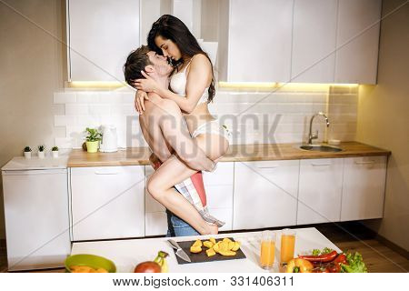 Young Sexy Couple Have Intimacy In Kitchen In Night. Hot Seductive Woman Sit On Mans Hands And Kiss