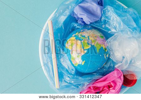 The Concept Of Reducing Plastic Bags Use: Modeled Globes Are Sunk In Many White Plastic Bags. Meanin