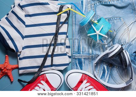 Red Gum Shoes, Jeans Shorts, Shirt, Red Starfish, Headphones And Cocktail Jar With Tube On Blue Flat