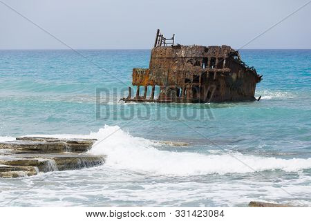 Rusty Ruined Ship Wreck Remainings In The Middle Of The Sea, Close To The Shore Of Cyprus.
