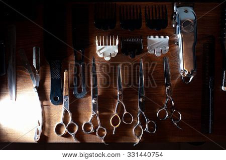 Scissors, Razor, Trimmer And Nozzles Lie On A Wooden Table, A Set Of Barber Equipment, Hairdresser T