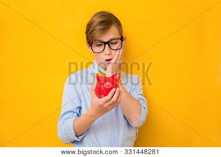 Business Man. Surprised Teenage Boy Holding A Red Piggy Bank. Business Concept. Saving Money Concept