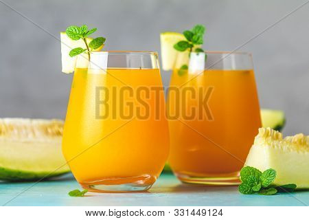 Yellow Orange Cocktail With Melon And Mint In Glass On Blue Concrete Background, Close Up. Summer Dr