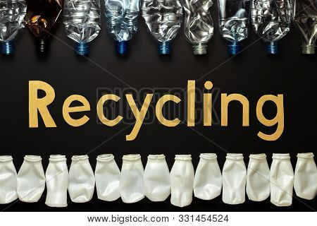 Recycling Concept. The Word Recycled From Cardboard Letters. Crumpled Bottles Made Of Polyethylene T