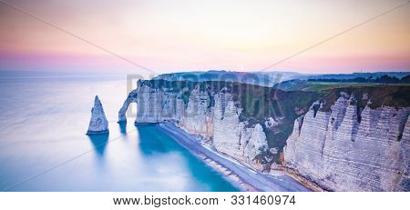 panorama of coastal landscape along the Falaise d'Aval the famous white cliffs of Etretat village with the Porte d'Aval natural arch and the rock known as the Aiguille d'Etretat