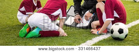 Coach Coaching Soccer Kids Soccer Team. Youth Sports Coach Using Tactics Board. Trainer Explaining M