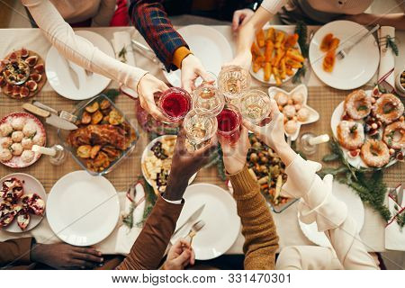 Top View Background Of People Raising Glasses Over Festive Dinner Table While Celebrating Christmas