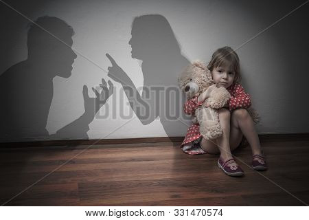 Divorce Concept. Sad Child Is Sitting At Floor When Parents Argue.