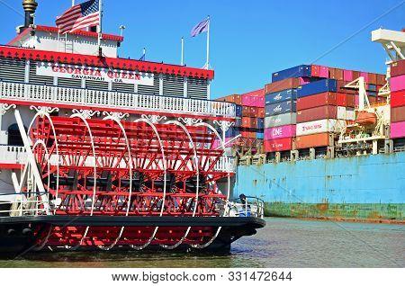 Savannah, Georgia - November 3, 2019 A Cargo Ship Passes By The Docked Riverboat Georgia Queen.